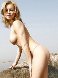 Blondie poses at a rocky seaside with not much panties on the advise of of