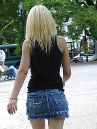 Blonde in black boots and tight blue jeans micro skirt posing into the open air