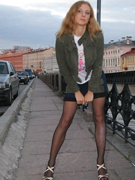 Sexy blonde in mini skirt and thigh swaggering stockings poses outside