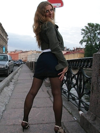 X blonde about miniature skirt with the addition of thigh overbearing stockings poses outside