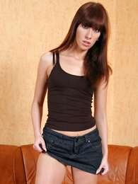 Tall with an increment of slender black-hearted with smarting legs poses in a denim mini skirt